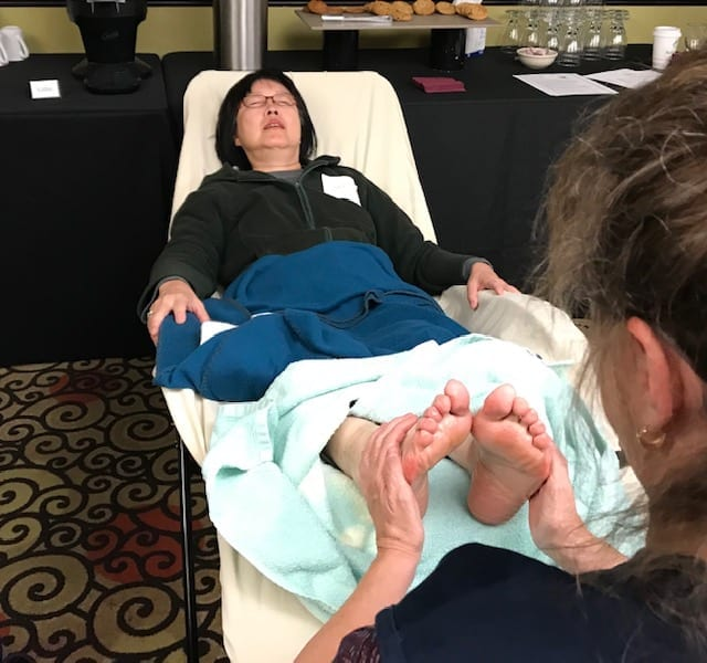 woman with green jacket gets a reflexology session