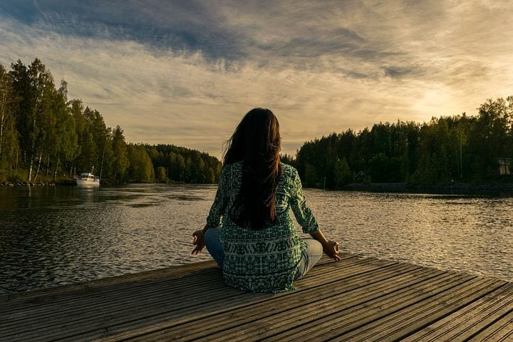 girl sitting on dock meditating